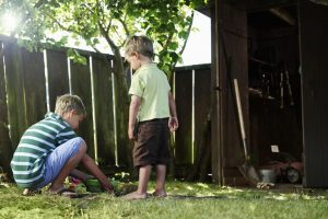 Two boys burying pet in their backyard